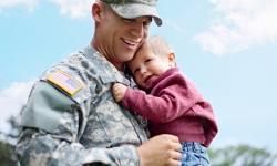 man in uniform holding baby